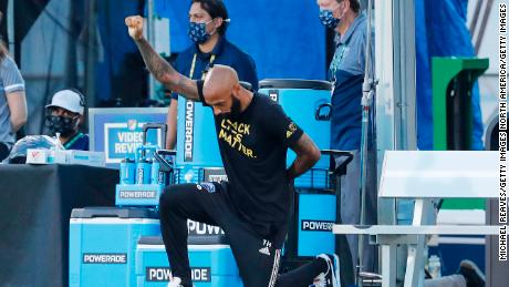 Head coach Thierry Henry of Montreal Impact takes a knee in support of the Black Lives Matter movement prior to a Group C match against Toronto FC as part of the MLS Is Back Tournament at ESPN Wide World of Sports Complex on July 16, 2020 in Reunion, Florida.