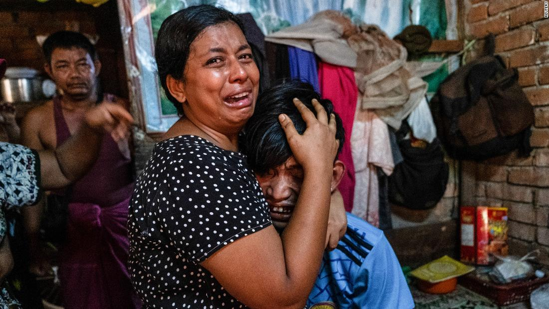 People cry in Yangon after a relative was shot during a crackdown on anti-coup protesters.