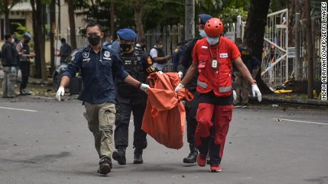 Indonesian police carry the remains of a suspected suicide bomber after an explosion outside a church in Makassar on March 28.