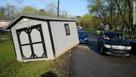 A vehicle passes a utility building that was carried onto a street by floodwaters Sunday, March 28, 2021, in Nashville.