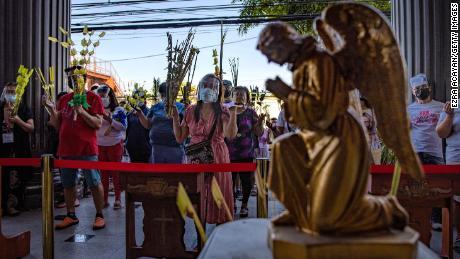 Filippinske katolikker iført masker og ansiktsskjold bærer palmeblader mens de ber utenfor en kirke for å feire palmesøndag 28. mars 2021 i Quezon City, Metro Manila, Filippinene.
