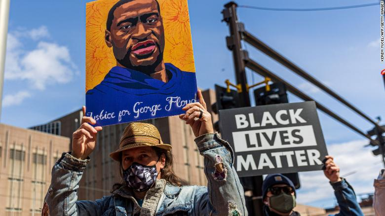 Demonstrators hold signs honouring George Floyd and other victims of racism as they gather during a protest outside Hennepin County Government Center on March 28, 2021 in Minneapolis, Minnesota. - Opening arguments begin on Monday in the trial of Derek Chauvin, the white police officer accused of killing George Floyd, a Black man whose death was captured on video and touched off protests against racial injustice across the United States and around the world. (Photo by Kerem Yucel / AFP) (Photo by KEREM YUCEL/AFP via Getty Images)
