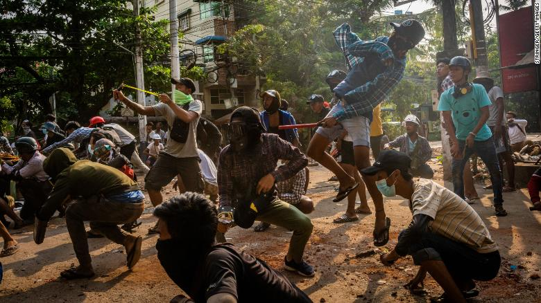 Anti-coup protesters use slingshots and pelt stones towards approaching security forces on March 28 in Yangon, Myanmar.