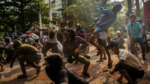 Protesters throw stones and use slingshots as security forces approached in Yangon on March 28.