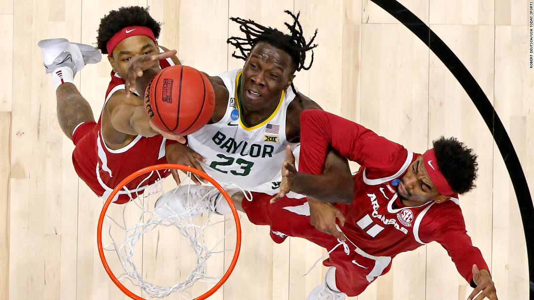 Baylor forward Jonathan Tchamwa Tchatchoua, center, goes for a rebound against Arkansas' JD Notae, left, and Jalen Tate.