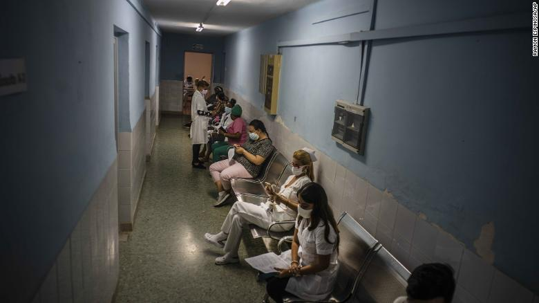 Healthcare workers sit in hallway as they wait to be injected with a dose of the Soberana-02 Covid-19 vaccine, in Havana, Cuba, March 24.