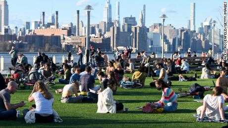 People sit in social distancing circles in Brooklyn's Domino Park with a view of the Manhattan skyline in the background on March 26, 2021.