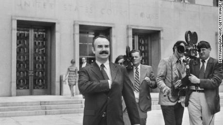 Former White House aide G. Gordon Liddy is filmed by journalists as he leaves US District Court, where he pleaded not guilty of breaking into Democratic National Headquarters at the Watergate Hotel.