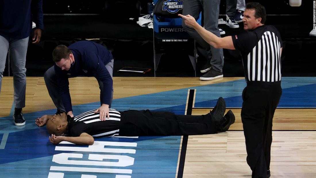 "Referee Bert Smith lies on the court after <a href=""https://www.cnn.com/2021/03/30/us/ncaa-gonzaga-usc-official-spt/index.html"" target=""_blank"">collapsing during the first half</a> of the Gonzaga-USC game. As he left the court on a gurney, he was sitting upright and appeared to be talking to a man walking beside him."