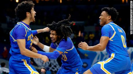 UCLA's Johnny Juzang, left, celebrates with Tyger Campbell, center, and Jaylen Clark after defeating Michigan in the Elite Eight round Tuesday.