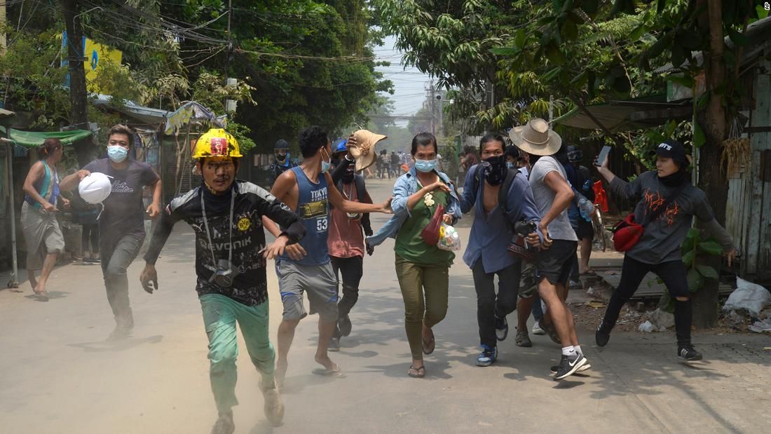 Protesters run to avoid the military in Yangon on March 30.