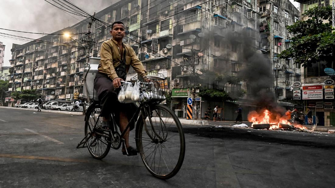 A man rides his bike as smoke billows from burning barricades in Yangon on March 30.