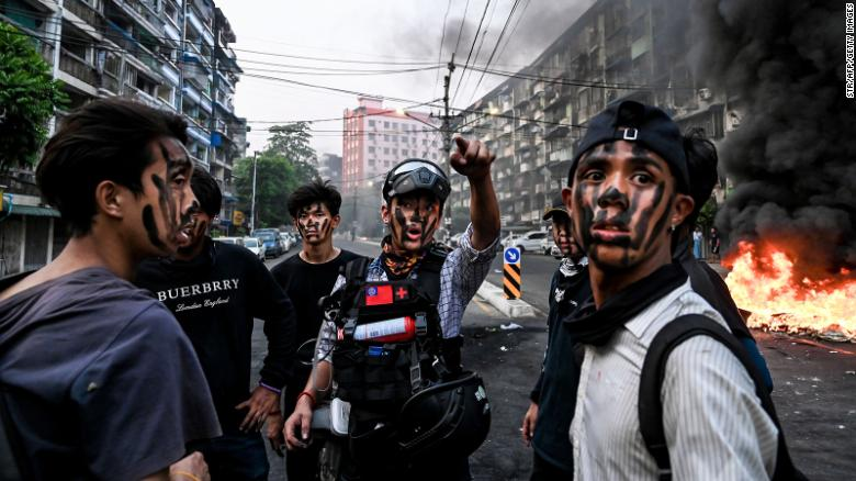 Protesters with their faces painted stand near a burning makeshift barricade during a protest against the military coup, in Yangon on Tuesday.