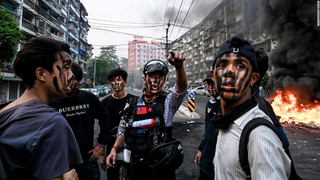 Protesters wearing face paint stand near a burning barricade during an anti-coup demonstration in Yangon on March 30.