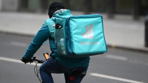 A Deliveroo rider cycles through central London on March 26, 2021. - The meal delivery platform Deliveroo is bracing for strikes and other social actions by disgruntled riders as it gears up for a major London stock listing.  The group has come under fire for employment conditions that have already scared off a couple of large institutional investors (Photo by DANIEL LEAL-OLIVAS / AFP) (Photo by DANIEL LEAL-OLIVAS/AFP via Getty Images)