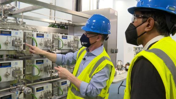 Mike McDermott, Pfizer's president of global supply, left, and CNN's Dr. Sanjay Gupta inside Pfizer's Kalamazoo, Michigan, manufacturing facility.