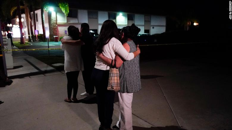 People comfort each other as they stand outside the Orange, California, business complex where the shooting occurred on Wednesday.
