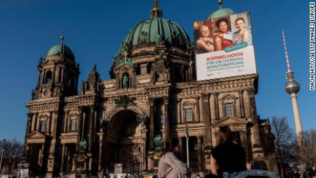 A vaccine campaign poster hangs at Berlin Cathedral.