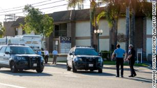 Officials work outside the Orange, California, business Thursday where four people, including a 9-year-old boy, were killed a day earlier.