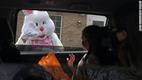 An Easter Bunny greets children during a Bunny Drive-Thru event outside in Alexandria, Virginia.