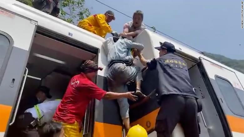 A passenger climbs out of the derailed train in Hualien County, Taiwan, on April 2.
