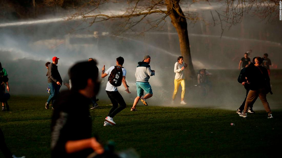 "People scatter as police fire water cannons to disperse a crowd at a park in Brussels, Belgium, on April 1. <a href=""https://www.cnn.com/world/live-news/coronavirus-pandemic-vaccine-updates-04-02-21/h_bc4daabf47fa48f57503c7de2e9b9aff"" target=""_blank"">Violent clashes broke out</a> between Brussels police and people gathering to attend a fake April Fool's Day festival that violated coronavirus restrictions."