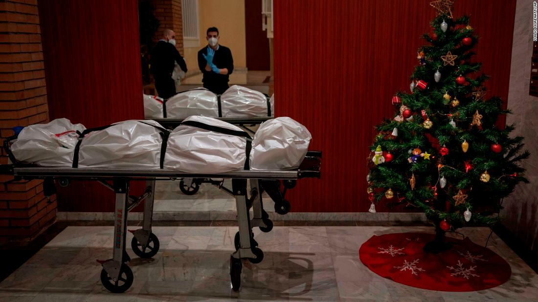 Mortuary workers take off their personal protective equipment after removing the body of a person who allegedly died of Covid-19 in Barcelona, Spain, on December 23.