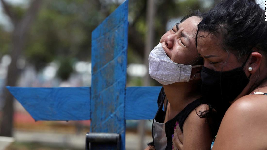 Kelvia Andrea Goncalves, left, is supported by her aunt Vanderleia dos Reis Brasao during the burial of her mother, Andrea dos Reis Brasao, in Manaus, Brazil, on January 17. Andrea, 39, died from Covid-19.