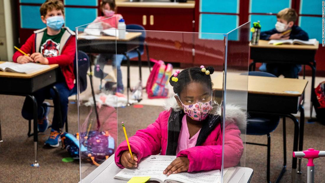 First-grader Sophia Frazier does her schoolwork behind a plastic divider at Two Rivers Elementary School in Sacramento, California, on March 8.