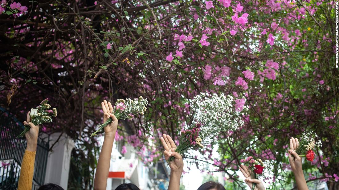 "People take part in a ""flower strike"" in Yangon on Friday, April 2."