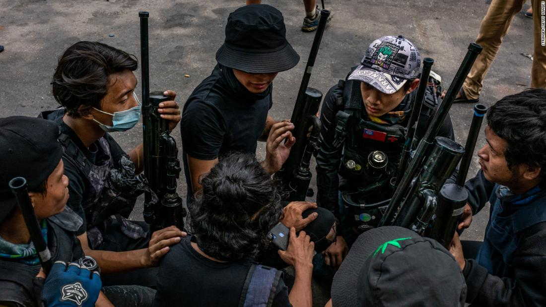 Protesters hold improvised weapons in Yangon on April 3.