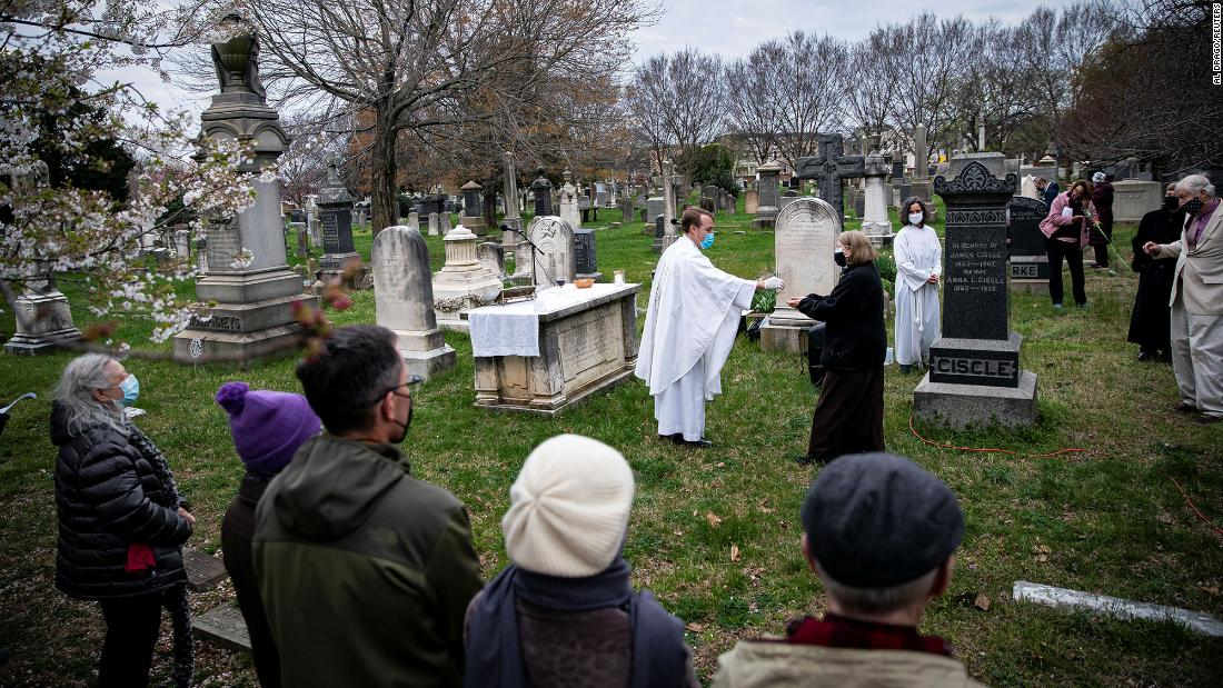 The Rev. John Kellogg, rector of Christ Church, wears a protective mask as he distributes communion at a sunrise Easter service held at the Congressional Cemetery in Washington, DC.