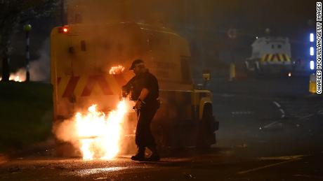 Police attend to a scene at Cloughfern as loyalist protesters hijack and burn vehicles on Saturday.