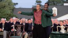 Woods puts on the Green Jacket in 2001 with the help of the previous year's champion Vijay Singh.