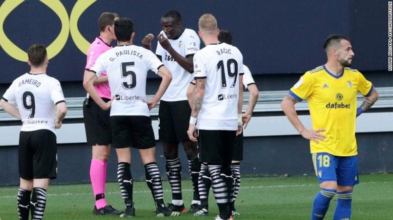 Valencia's defender Diakhaby (middle) talks with the referee  after allegedly receiving a racist comment by Cadiz's defender Juan Cala (unseen).