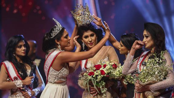 In this photograph taken on April 4, 2021, winner of Mrs. Sri Lanka 2020 Caroline Jurie (2-L) removes the crown of 2021 winner Pushpika de Silva (C) as she is disqualified by the jurie over the accusation of being divorced, at a beauty pageant for married women in Colombo. (Photo by - / AFP) (Photo by -/AFP via Getty Images)