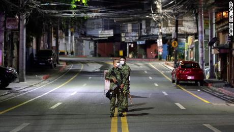 Armed policemen stand at an empty road on March 15 in Metro Manila, Philippines.