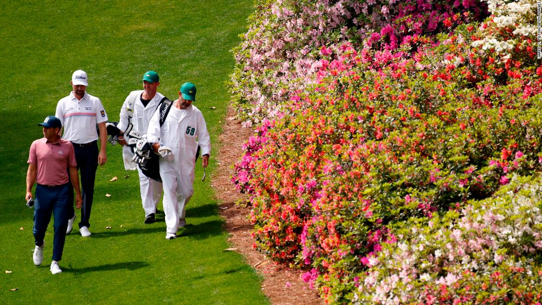 Sergio Garcia, Webb Simpson and their caddies walk to the sixth green on Thursday.