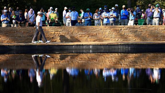 McIlroy and Thomas walk across the Sarazen Bridge during a practice round on Tuesday.