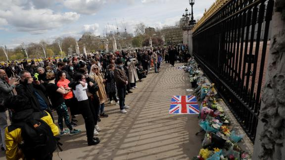 People view flowers left in front of the gate at Buckingham Palace in London, after the announcement of the death of Britain's Prince Philip, Friday, April 9, 2021. Buckingham Palace officials say Prince Philip, the husband of Queen Elizabeth II, has died. He was 99. Philip spent a month in hospital earlier this year before being released on March 16 to return to Windsor Castle.