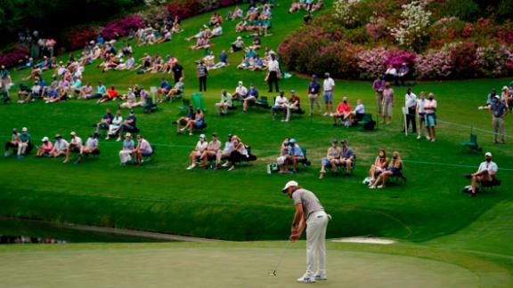 People spread out from one another as they watch Tommy Fleetwood putt on the 16th green on Friday.