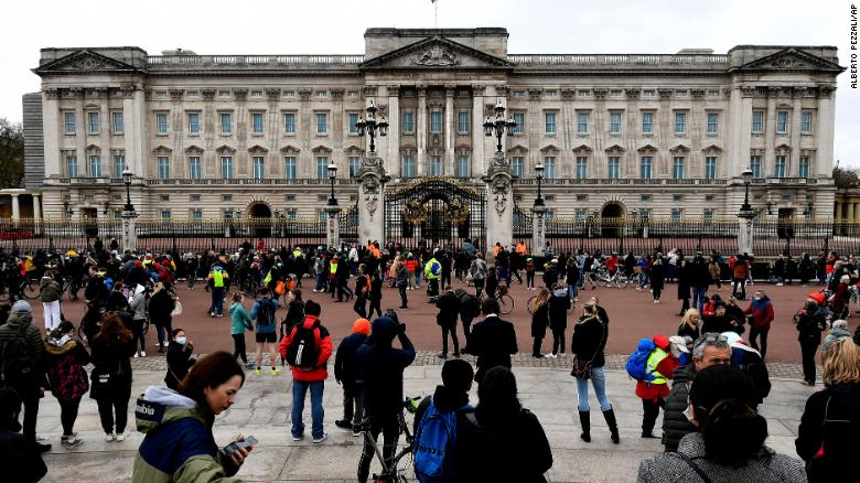 People gather outside the gates of Buckingham Palace in London on Saturday.