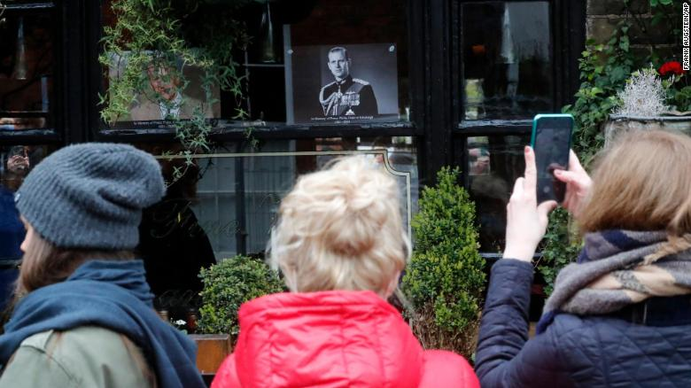 People take cellphone photos of a portrait of Prince Philip in a pub window near Windsor Castle on Saturday.