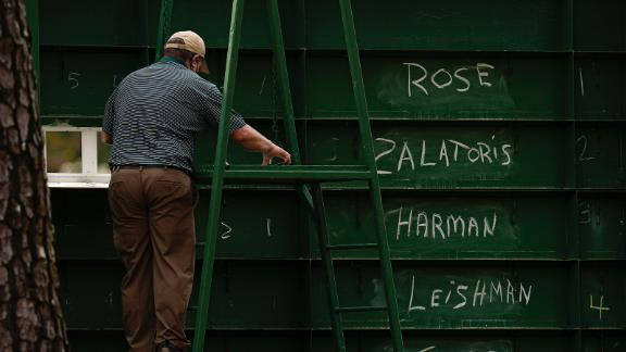 An attendant adjusts scores from behind a leaderboard on Saturday.