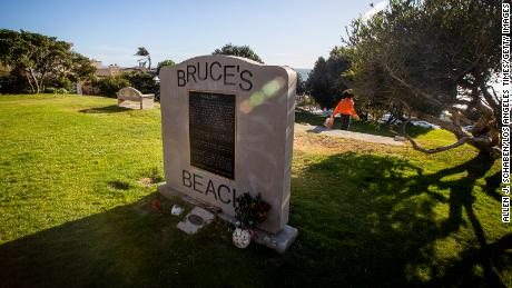 The Bruce's Beach plaque is at the top of a hill, with the lifeguard building below.