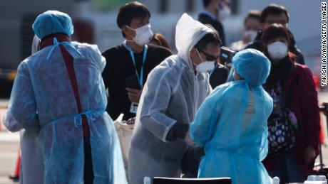 Workers check the temperature of passengers disembarking the quarantined Diamond Princess cruise ship in February 2020