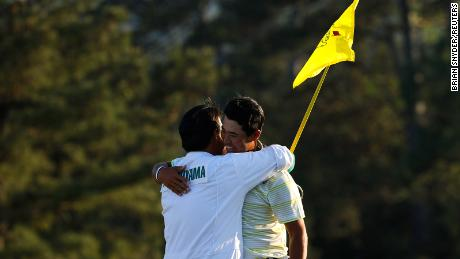 Matsuyama celebrates with his caddie on the 18th green after winning The Masters.