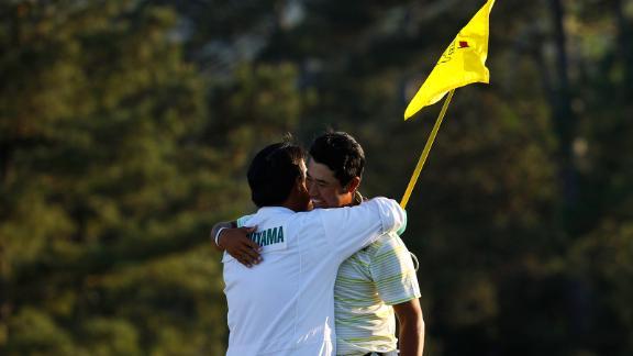 Matsuyama celebrates with his caddie, Shota Hayafuji, on the 18th green Sunday.