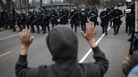 A person raises their hands as police approach near the site where Daunte Wright was shot in Brooklyn Center, Minnesota.