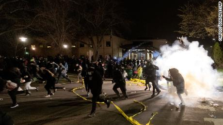 Officers try to disperse the crowd at the Brooklyn Center Police Department late Sunday night.
